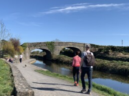 People strollng along path beside Royal Canal in sunshine